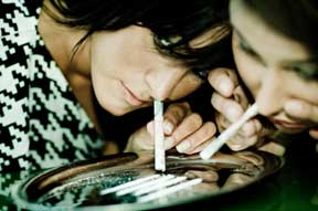 Two women snorting cocaine on a sylver platter