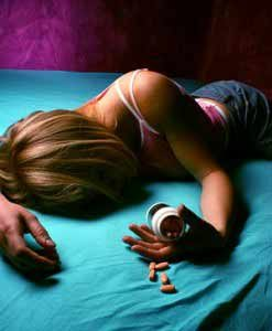 Woman lying on bed with spilled pills